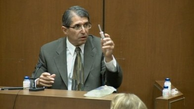 PHOTO: Witness for the Conrad Murray trial, Dr. Paul White, does a demonstration in court right with IV bags and syringes.