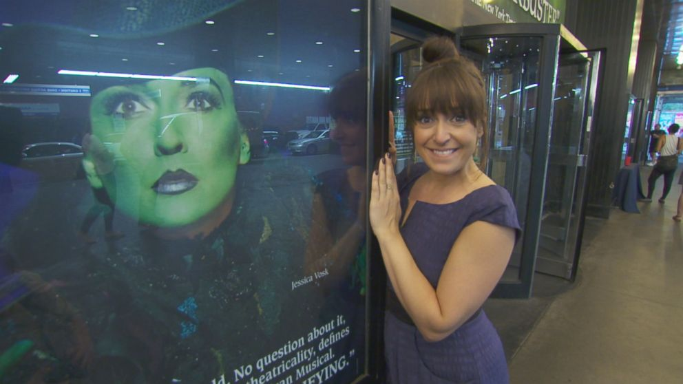 Broadway star Jessica Vosk is seen here posing next to a Wicked poster showing her as her character, Elphaba.