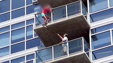 PHOTO: Stuntmen rushed into an apartment building to rescue a woman who was dangling from the balcony of the 14th floor.