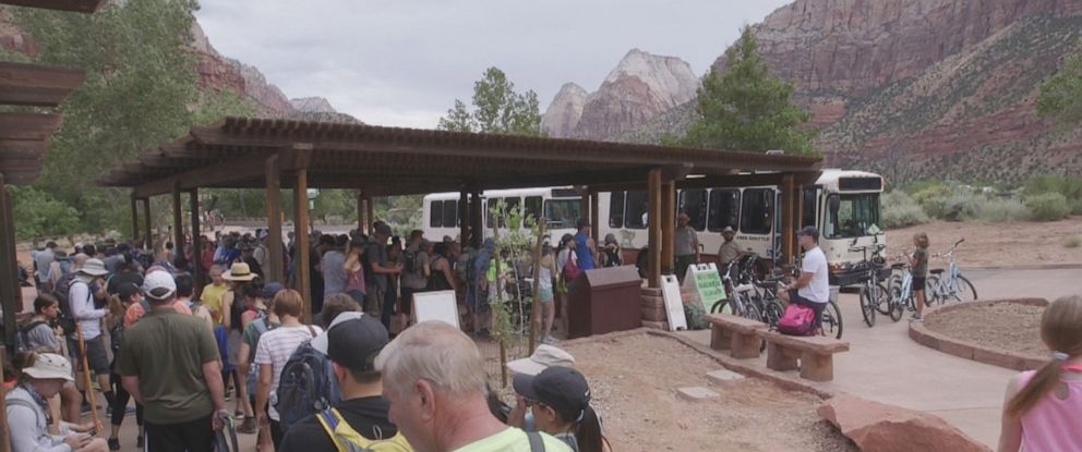 PHOTO: Crowds at Zion National Park wait in line to board a shuttle bus.
