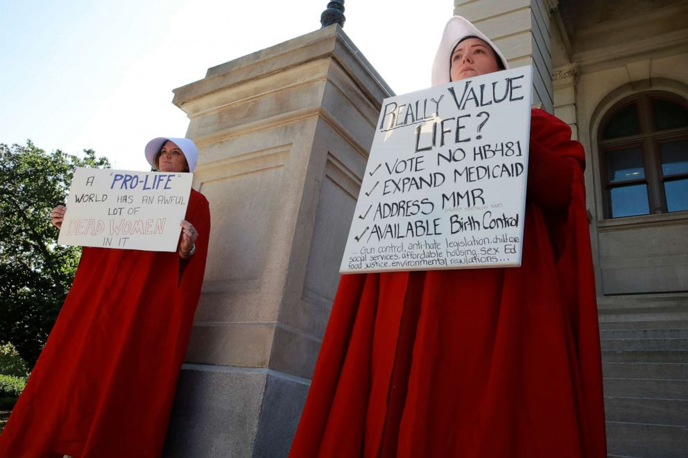 PHOTO: April Houston and Lara Martin hold signs while dressed as Handmaids in protest of Georgias anti-abortion heartbeat bill at the Georgia State Capitol in Atlanta, May 7, 2019.