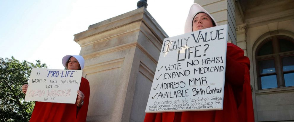 """PHOTO: April Houston and Lara Martin hold signs while dressed as Handmaids in protest of Georgias anti-abortion """"heartbeat"""" bill at the Georgia State Capitol in Atlanta, May 7, 2019."""