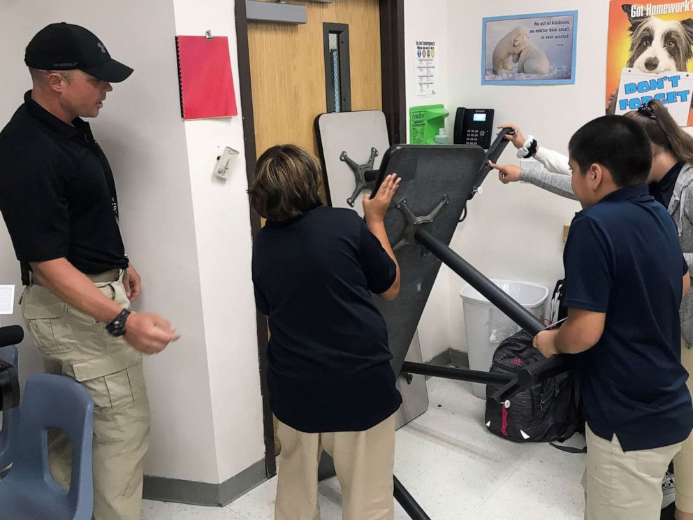 PHOTO: Joe Deedon, owner of Tac One Consulting, instructs sixth graders at Pinnacle Middle School in Denver how to barricade a classroom to stop an active shooter.