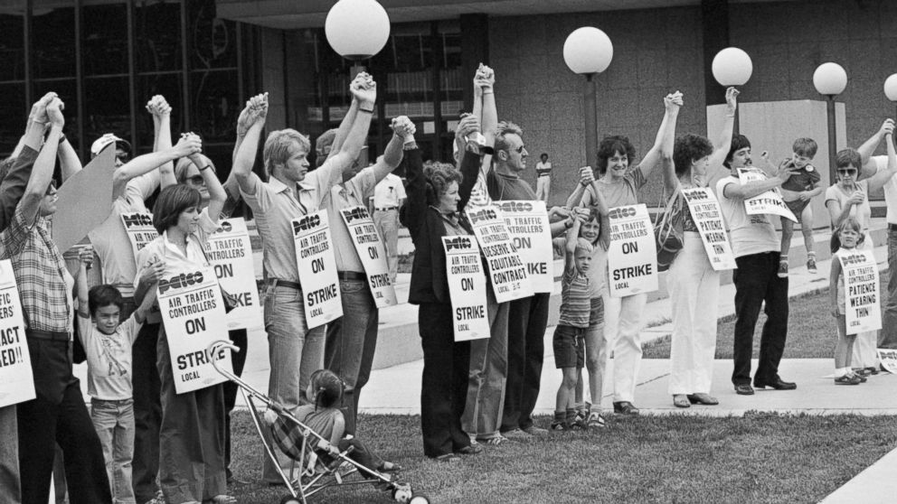 Members of PATCO, the air traffic controllers union, hold hands and raise their arms as their deadline to return to work passes. All strikers were fired on the order of President Reagan on Aug. 5, 1981.