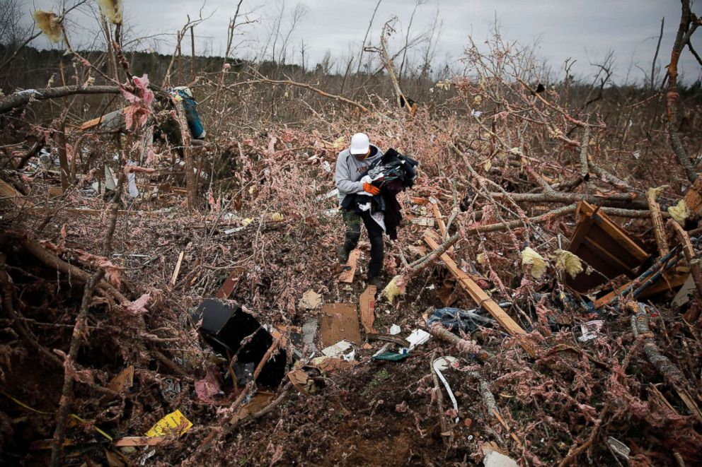PHOTO: Dax Leandro salvages clothes from the wreckage of his guests home after two support-to-support tornadoes touched down, in Beauregard, Ala., March four, 2019.
