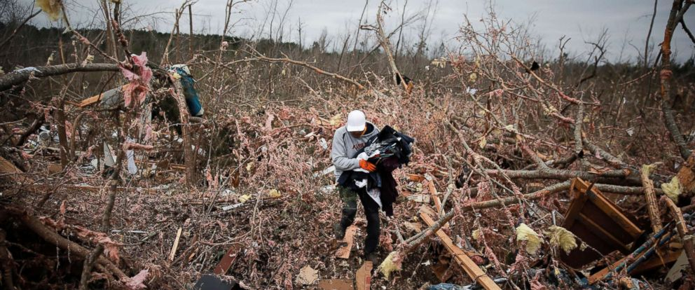 PHOTO: Dax Leandro salvages clothing from the wreckage of his friends home after two back-to-back tornadoes touched down, in Beauregard, Ala., March 4, 2019.
