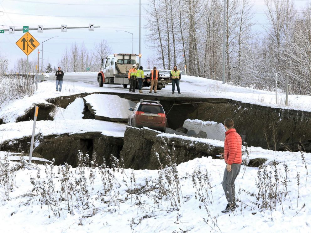 PHOTO: Highway workers and spectators look at a car stuck on a section of an off-ramp that collapsed during an earthquake in Anchorage, Ala., Nov. 30, 2018.