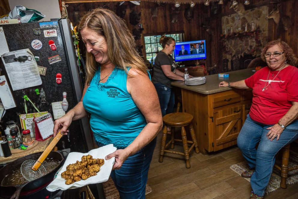 PHOTO: Cooking fried alligator meat, Julie Harter prepares dinner with her family, including daughter Monica and mother Ellen, right, at her home in Lakeland, Fla.