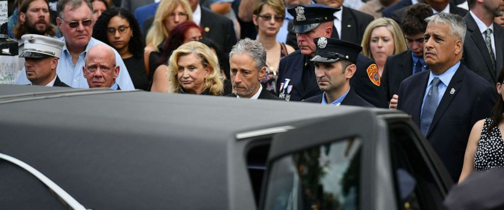 PHOTO: Jon Stewart and Congresswoman Carolyn B. Maloney stand with other attendees as the hearst carrying former NYPD Detective and 9/11 first responder, Luis Alvarez passes during his funeral service in New York City, July 3, 2019.