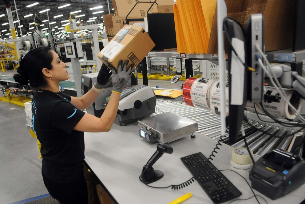 PHOTO: An Amazon associate processes a package for delivery at the newest Amazon Robotics fulfillment center during its first public tour, April 12, 2019, in Orlando, Florida.