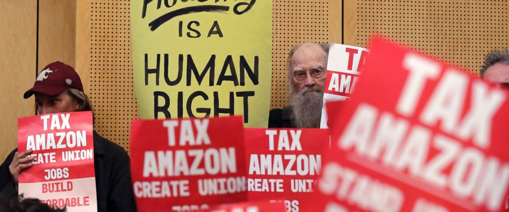 PHOTO: Members of the public look on at a Seattle City Council before the council voted to approve a tax on large businesses such as Amazon and Starbucks to fight homelessness, May 14, 2018, in Seattle.