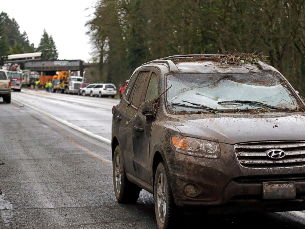 PHOTO: A car covered in mud and debris with a smashed windshield and other damage sits parked on the shoulder just beyond where an Amtrak train derailed onto Interstate 5, Dec. 18, 2017, in DuPont, Wash.