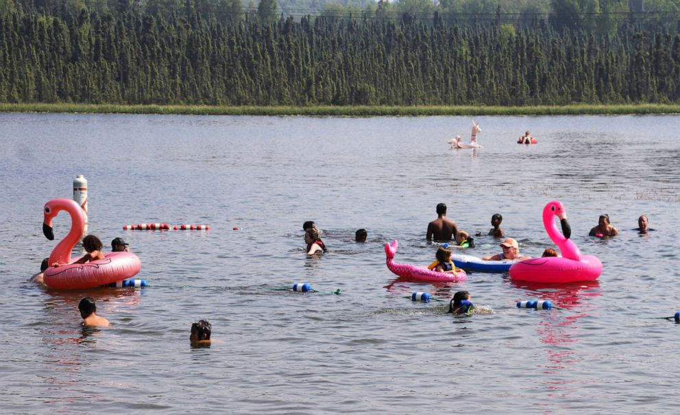 PHOTO: Children play with inflatable flamingos and other creatures at Goose Lake on July 5, 2019, in Anchorage, Alaska.