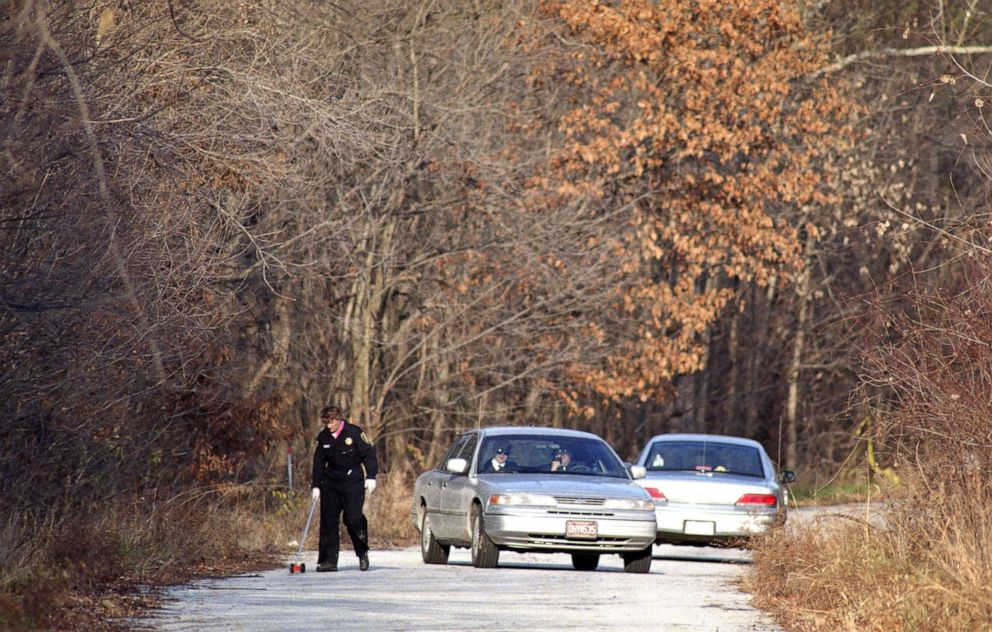 PHOTO: Police detectives and sheriffs deputies near the scene in St. Charles County, Mo., where a body believed to be Angie Housmans was found on Nov. 27, 1993.