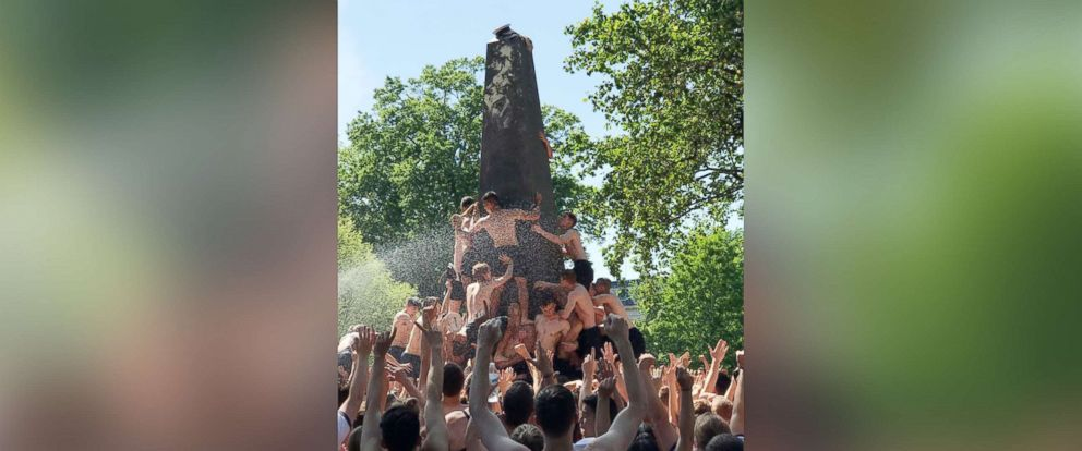 PHOTO: Freshmen at the U.S. Naval Academy in Annapolis, Md., attempt to climb a greased monument in a photo posted to Facebook by the school on May 21, 2018.