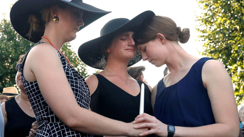 Three daughters of Wendi Winters, Winters, Summerleigh and Montana Geimer hold each other during a candlelight vigil held near the Capital Gazette, the day after a gunman killed five people (including Wendi Winters) inside the newspaper's building in Annapolis, Md., June 29, 2018.
