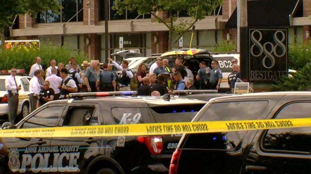 Officials and first responders gather outside an office building at 888 Bestgate Road in Annapolis, Md., after reports of a shooting in the offices of the Capital Gazette newspaper, June 28, 2018.