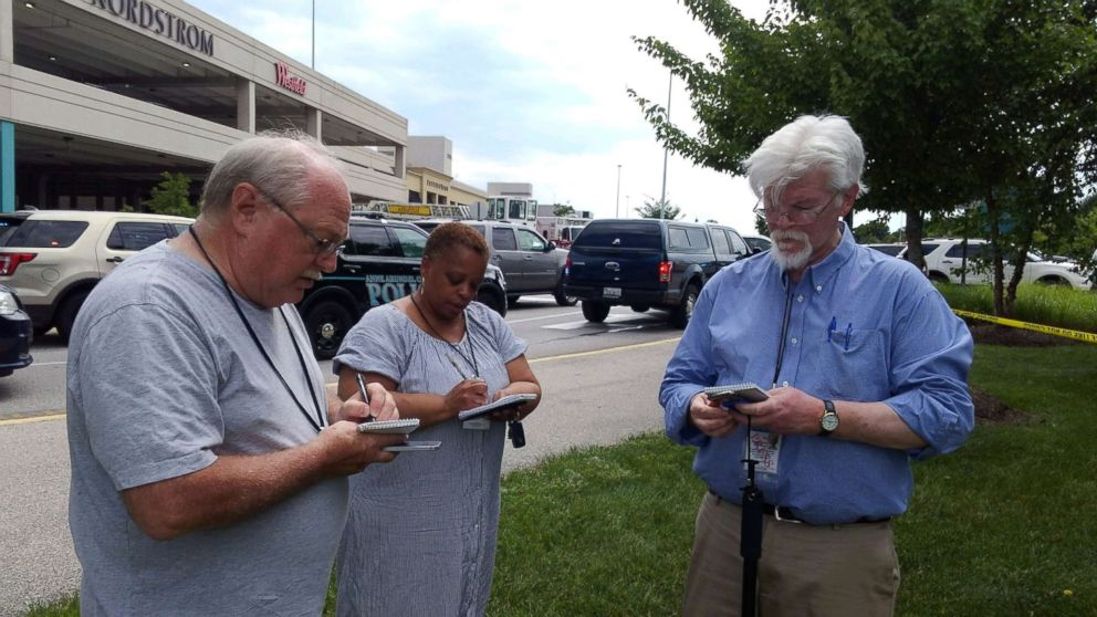 """Capital Gazette journalist E.B. """"Pat"""" Furgurson III takes notes with two other people as police officers respond to a shooting inside Capital Gazette offices in Annapolis, Md., June 28, 2018."""