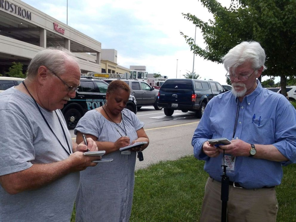 PHOTO: Capital Gazette journalist E.B. Pat Furgurson III takes notes with two other people as police officers respond to a shooting inside Capital Gazette offices in Annapolis, Md., June 28, 2018.