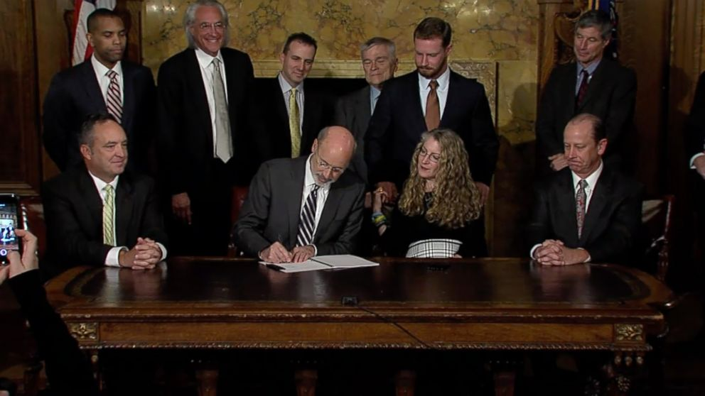 Pennsylvania Gov. Tom Wolf signs the anti-hazing law surrounded by lawmakers and the family of Tim Piazza.