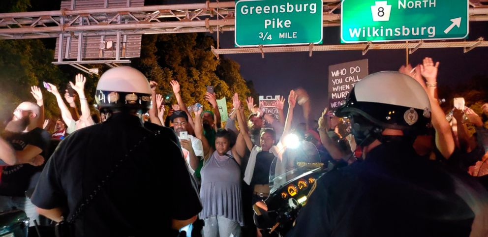 PHOTO: Protesters chant Hands up! Dont shoot! at motorcycle officers near the head of a line of vehicles stuck on Interstate 376 in Pittsburgh, June 21, 2018 for the death of Antwon Rose.