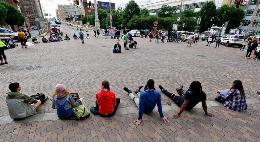 Marchers sit down at the intersection of Grant Street and the Boulevard of the Allies and stop traffic as they protest the shooting death of Antwon Rose Jr. on Tuesday, June 26, 2018, in Pittsburgh.