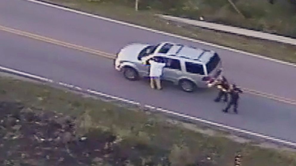 In this Sept. 16, 2016 image made from video provided by police, Terence Crutcher, left, with his arms held up, is pursued by police officers as he walks next to his stalled SUV moments before he was shot and killed by one of the officers in Tulsa, Okla.