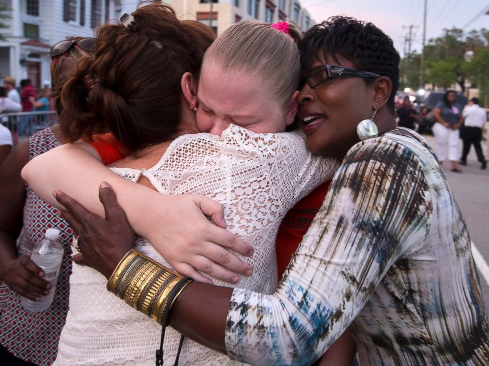 PHOTO: J. Denise Cromwell, left, hugs her daughter, Asia Cromwell, center, and a friend Sandy Teckledburg outside the Emanuel AME Church after a memorial in Charleston, S.C., June 19, 2015.