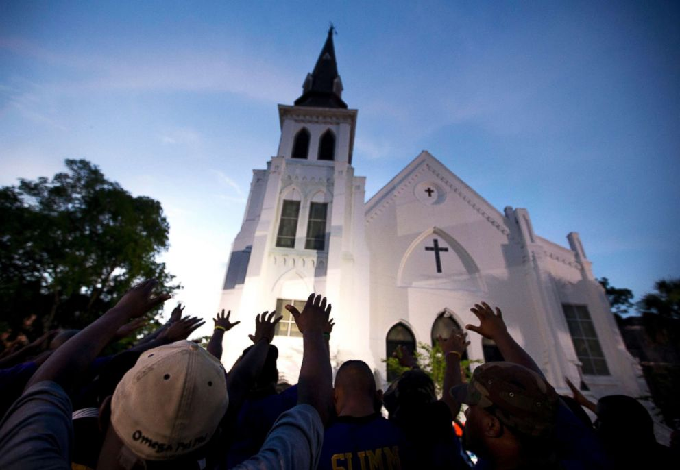 Men from Omega Psi Phi Fraternity Inc. lead a crowd of people in prayer outside the Emanuel AME Church in Charleston, S.C., June 19, 2015.