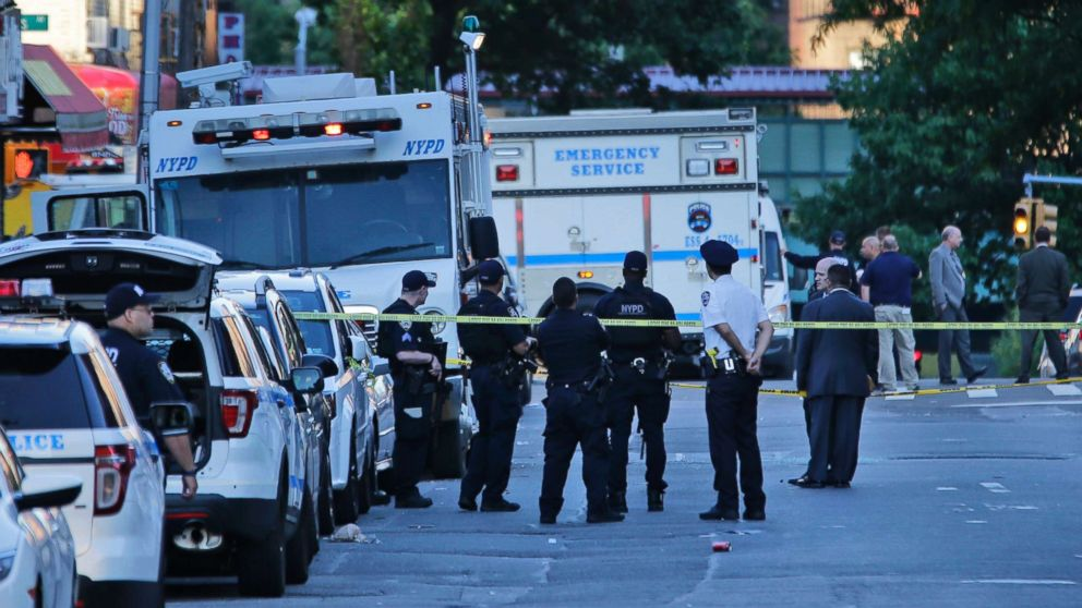 Emergency personnel stand near the scene where a police officer was fatally shot while sitting in her patrol car in the Bronx section of New York, July 5, 2017.
