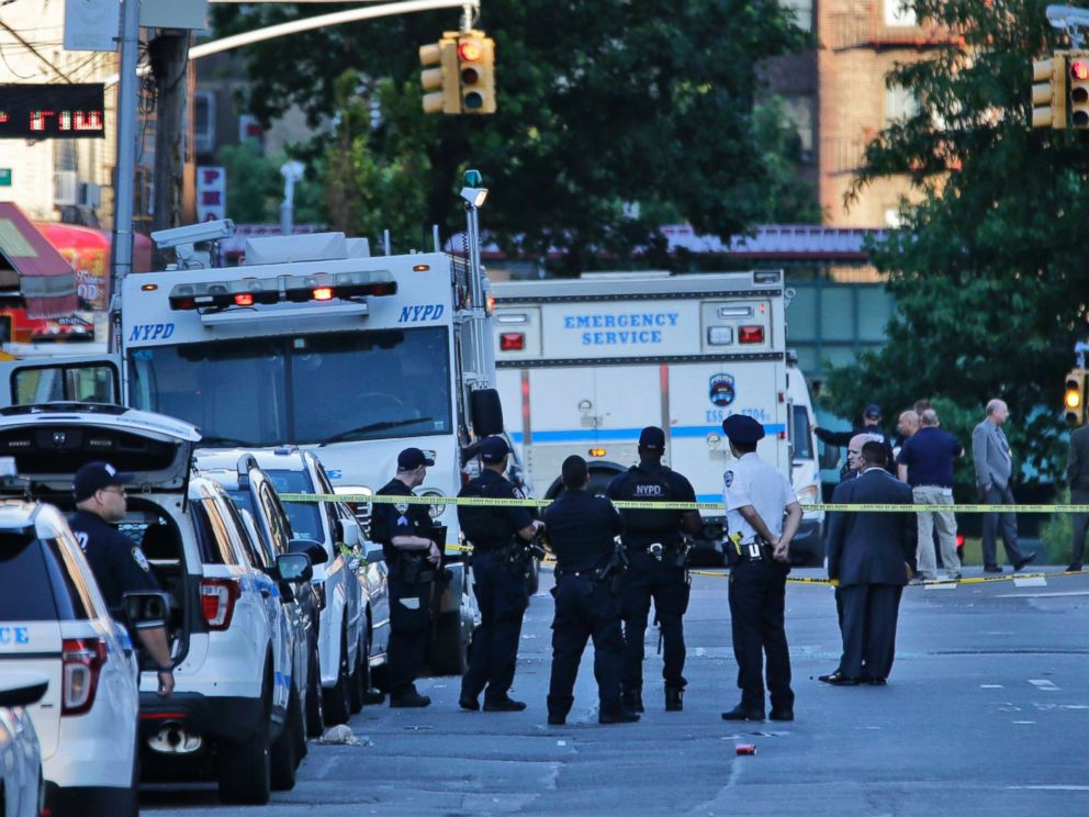 PHOTO: Emergency personnel stand near the scene where a police officer was fatally shot while sitting in her patrol car in the Bronx section of New York, July 5, 2017.