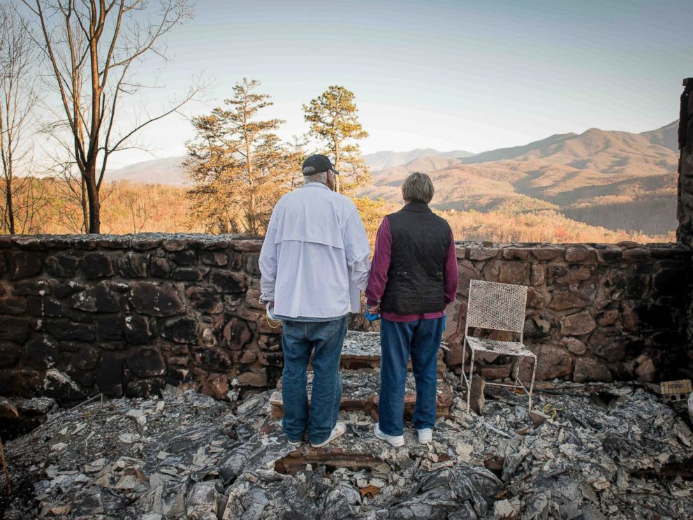 PHOTO: Richard T. Ramsey and Sue Ramsey hold hands while looking at the skyline from the remains of their house of 41 years, Dec. 1, 2016, in Gatlinburg, Tennessee.