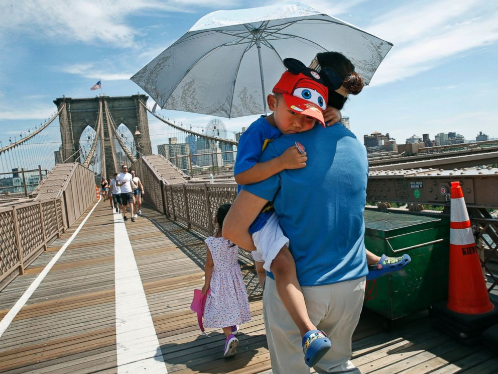 PHOTO: In this July 24, 2016, file photo, Xiuquin Huang carries her grandson Ruize Yan beneath an umbrella as she walks across the Brooklyn Bridge with her daughter and granddaughter Rina Wu.