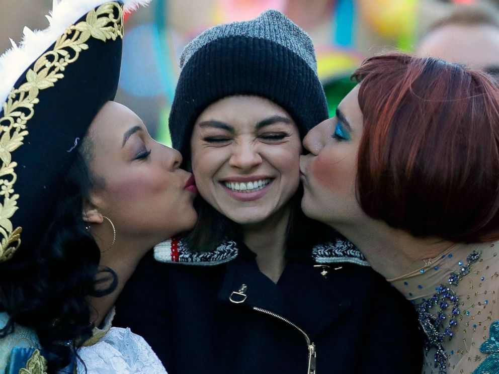 Actress Mia Kunis, center, is kissed by Amira Weeks, left, and Jacques Berguig, right, during a parade for Kunis in Cambridge, Thursday, Jan. 25, 2018. Kunis was honored as Woman of the Year by the Hasty Pudding Theatricals at Harvard University.
