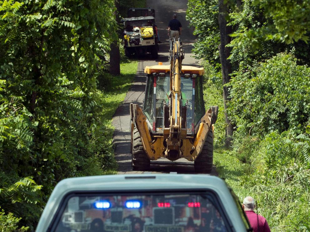 PHOTO: Construction equipment and law enforcement officials head down a blocked off drive way, July 10, 2017, in Solebury, Pa.