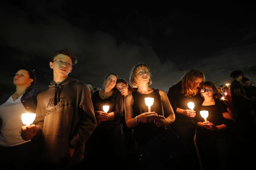 People participate in a candlelight vigil in memory of the 17 students and faculty who were killed in the Wednesday mass shooting at Marjory Stoneman Douglas High School in Parkland, Fla., Monday, Feb. 19, 2018.