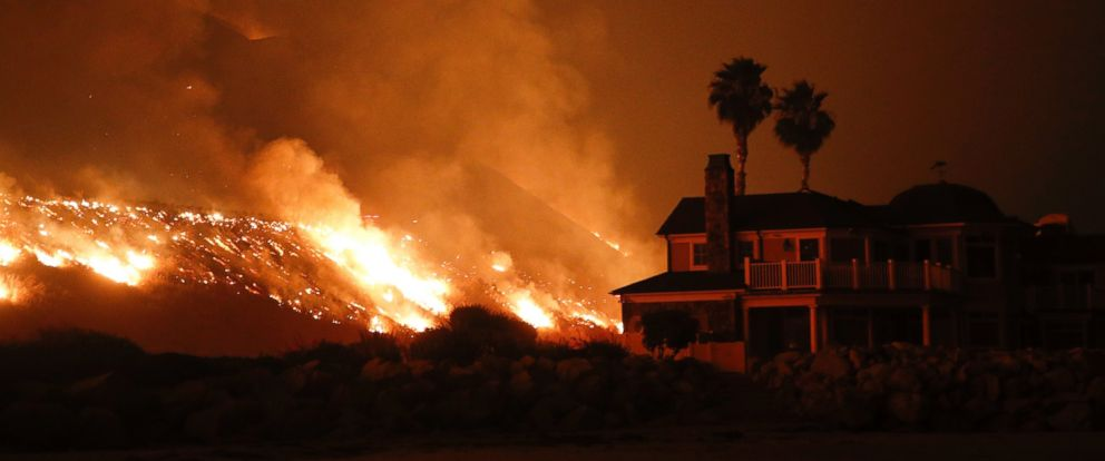 A wildfire threatens homes as it burns along the 101 Freeway Tuesday, Dec. 5, 2017, in Ventura, Calif., raked by ferocious Santa Ana winds.