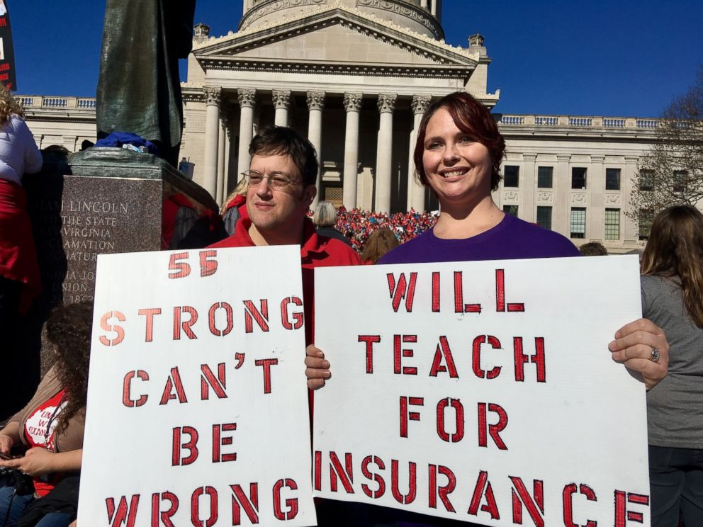 Teachers John and Kerry Guerini of Fayetteville, West Virginia, hold signs at a rally at the state Capitol in Charleston, W.Va., Monday, Feb. 26, 2018. Teachers across West Virginia will continue a walkout over pay and benefits for a fourth day.