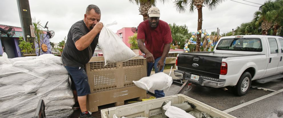 PHOTO: Jerry Boyd, left, and Tommy Neal unload sandbags that will be used to shore up doorways at a restaurant as they prepare for Tropical Storm Hermine, Wednesday, Aug. 31, 2016, in Cedar Key, Fla.