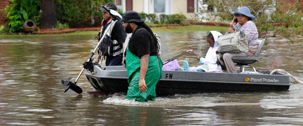 PHOTO: Volunteers pull a boat with a woman and young child as they evacuate from their homes Saturday, Aug. 13, 2016, in Baton Rouge.