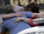 PHOTO:A group of people huddle together after an explosion and gunshots were heard near the scene where a man was holding four firefighters hostage Wednesday, April 10, 2013 in Suwanee, Ga.