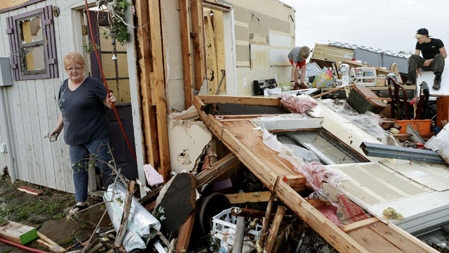 PHOTO: Marlena Hodson walks out of her home as her grandsons, Campbell Miller, 10, and Dillon Miller, 13, at right, help her sort through belongings after a tornado damaged her home Carney Okla., on Sunday, May 19, 2013.