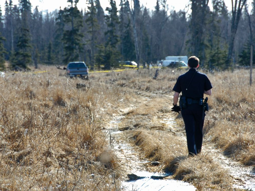 PHOTO: On March 22, 2015, a Kenai police officer walks down a trail leading to a temporary camp where police and Federal Bureau of Investigations personnel are working to identify human remains.
