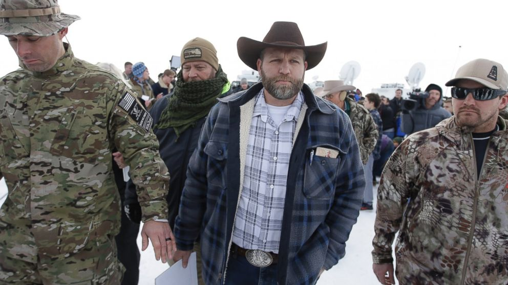 Ammon Bundy, center, walks off after speaking with reporters during a news conference at Malheur National Wildlife Refuge headquarters, Jan. 4, 2016, near Burns, Ore.