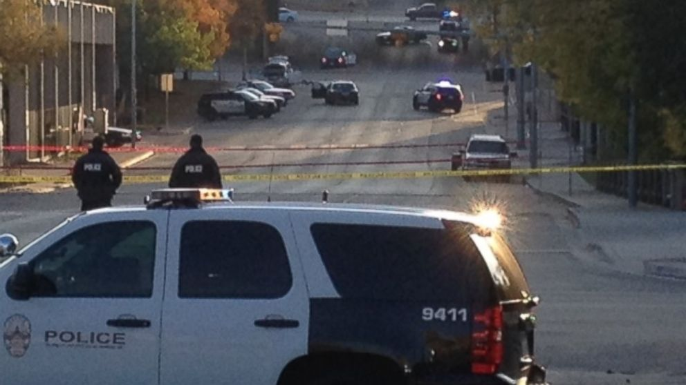 Police tape marks off the scene after authorities shot and killed a man who they say opened fire on the Mexican Consulate, police headquarters and other downtown buildings on Nov. 28, 2014 in Austin, Texas. In the distance, police cars surround the suspect's vehicle parked near the Interstate 35 overpass.
