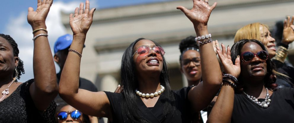 PHOTO: A woman sings at a rally led by faith leaders outside City Hall, Sunday, May 3, 2015, in Baltimore.