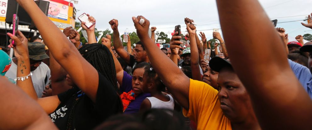 PHOTO: People hold up their fists at a vigil outside the Triple S convenience store in Baton Rouge, La., Wednesday, July 6, 2016. Alton Sterling, 37, was shot and killed outside the store by Baton Rouge police, where he was selling CDs.
