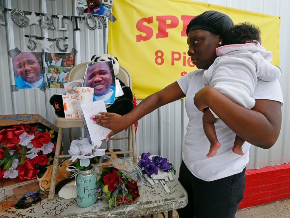 PHOTO: Shermire Reed, holding her daughter Zoe, places a card at a makeshift memorial outside a convenience store in Baton Rouge, Louisiana, July 6, 2016.