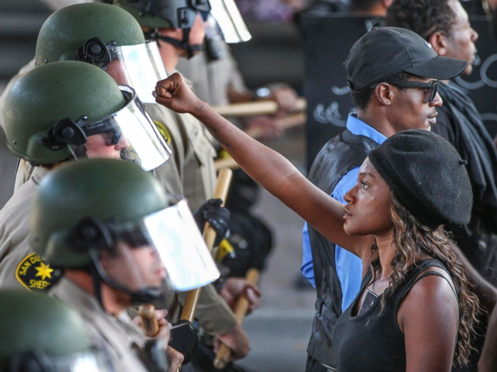 PHOTO: Ebonay Lee holds up her fist toward a line of Sheriffs deputies as she and other people protest Wednesday, Sept. 28, 2016, in El Cajon, Calif.