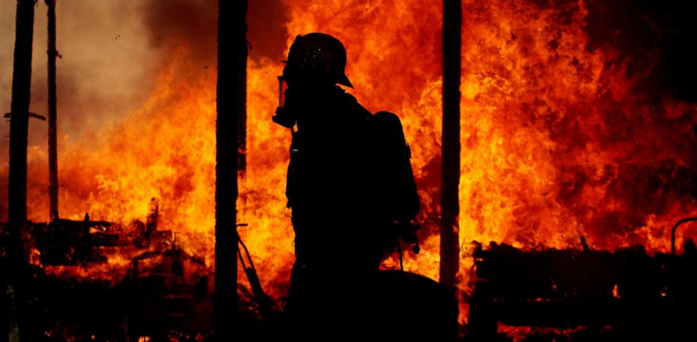 PHOTO: This Jan. 14, 2014 photo shows a Riverside County firefighter walking past a fully engulfed burning home in Jurupa Valley, Calif.